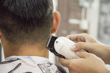 Haircut men Barbershop. Men's Hairdressers; barbers. Barber cuts the client machine for haircuts. Foto de archivo
