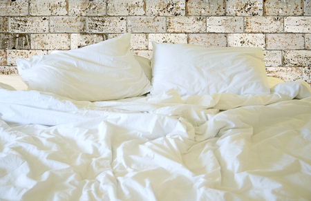 Messy white bed and pillow, in the morning