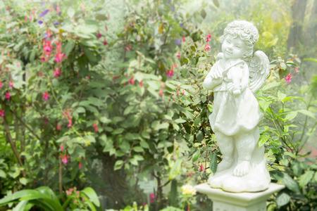Young Angel Sculpture in garden Banco de Imagens