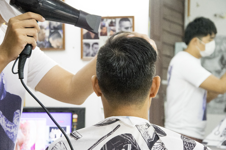 Close up of a man hairdresser with hair dryer at barbershop. hairdresser drying hair of a man