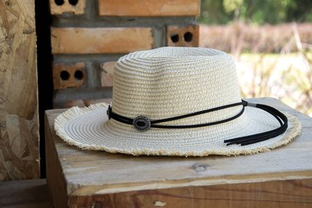 White cowboy hat on a wooden table.
