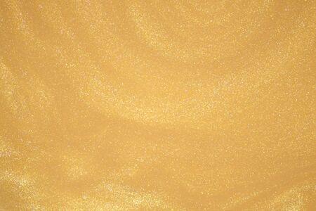 Golden glitter dust on dark background.