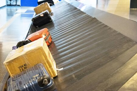 Wheeled suitcase on a luggage belt at the airport terminal. 免版税图像