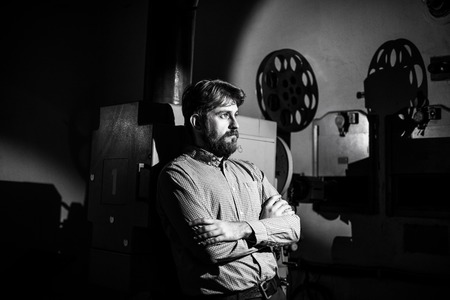 retro dark: beautiful hipster man standing near a film projector in the room projectionist Stock Photo