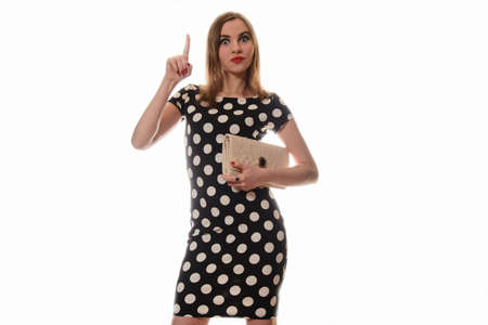 polka dot dress: Surprised girl in a polka dot dress and clutch points to the top