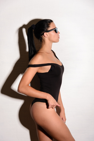 black ass: Young beautiful woman with slim body and sexy ass posing in black swimsuit  in studio