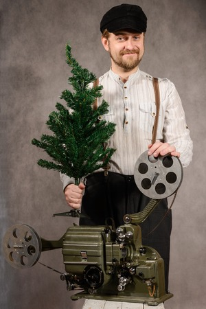 hristmas: ?heerful projectionist with ?hristmas tree in their hands with a film projector on a gray background in the studio