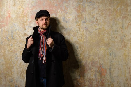 trench coat: image of a caucasian man with grungy blond hair dressed warmly in a stylish black trench coat and a funky hat and scarf for the cold winter Stock Photo