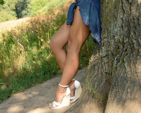 girl in shorts and white shoes posing near wood in nature
