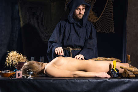medieval medicine: Portrait of a crazy medieval scientist working in his laboratory. Alchemist. Halloween. Stock Photo