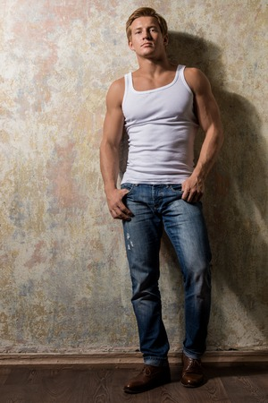 dirty blond: Beautiful  gay in white t-shirt posing against grunge background Stock Photo