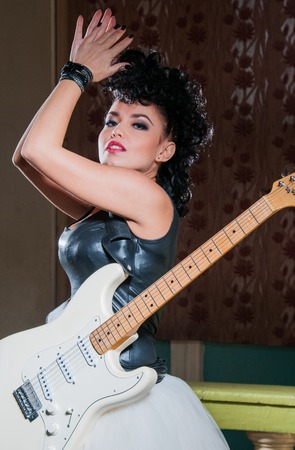 heavy metal: Photo of a female guitarist playing an electric guitar. Stock Photo