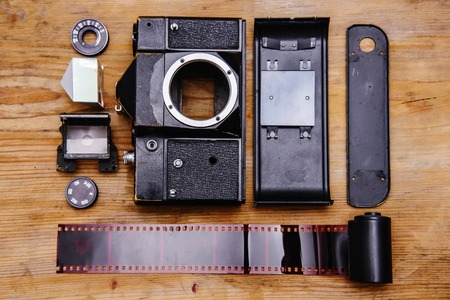 space for type: Disassembled rangefinder camera. isolated on wooden background.