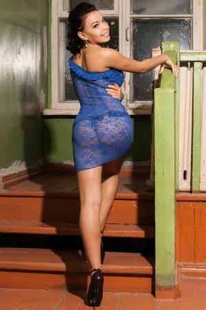 aantrekkelijk meisje in een blauw transparante jurk staande op de stappen terug