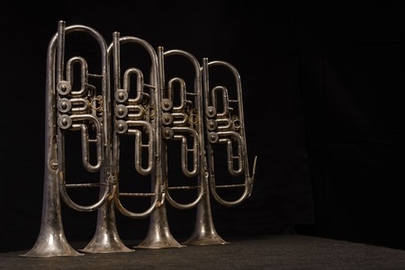 wind instrument: Four old brass wind instrument stand on a table on a black background