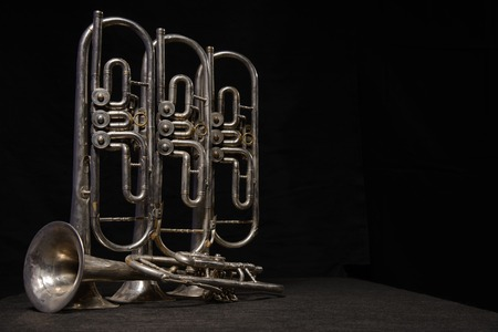brassy: Four old brass wind instrument stand on a table on a black background