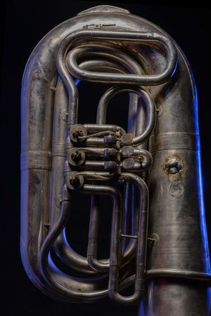 tuba: fragment of silver tuba isolated on black background