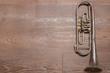 jazzy: Old rusty trumpet lays on wooden floor