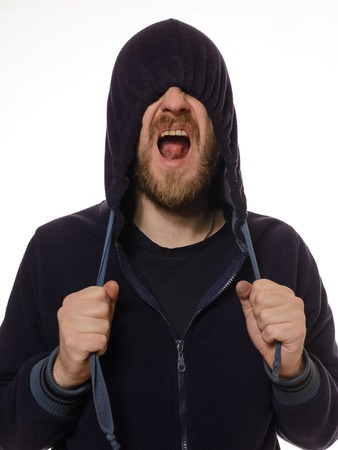 unleashed: Unleashed emotions. Young man covering his face by blue hood and shouting while standing against white background Stock Photo