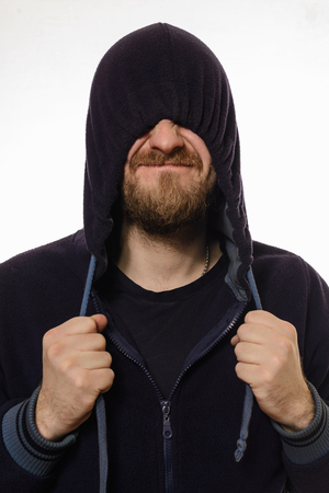 pulled over: beard man pulled a hood over his eyes and smile while standing against white background Stock Photo