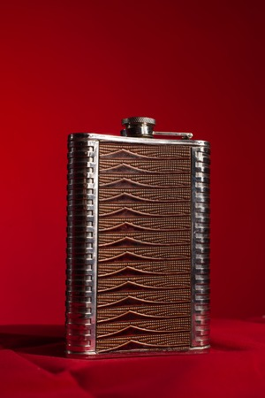 hip flask: Stainless hip flask isolated on a red background