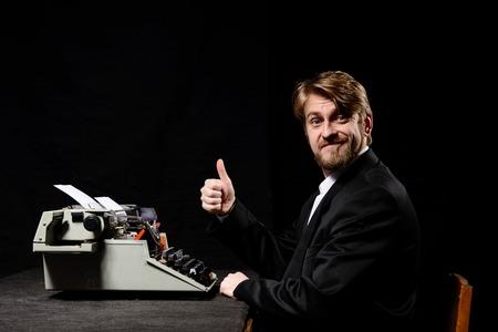 schrijver, een man in een zwarte jas typen op de typemachine op een zwarte achtergrond
