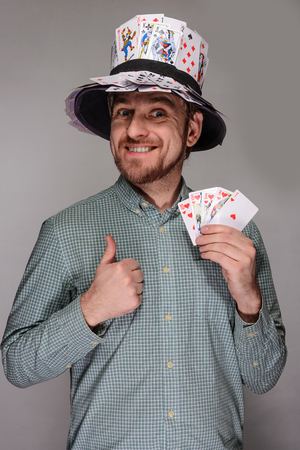 male facial: man in the hat of playing cards on gray background Stock Photo