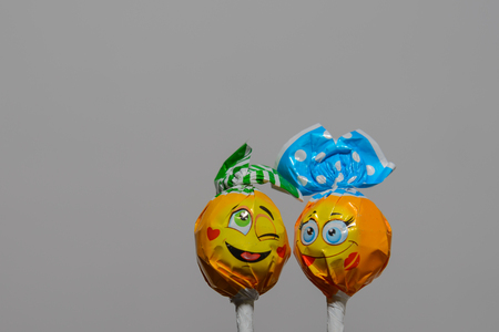 wrappers: two Chupa Chups style candy in wrappers smilies on gray background