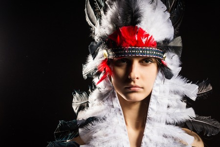 native american headdress: Beautiful young native American Indian woman on black background