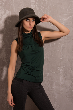 full shot: Portrait of young sexy woman in shirt, hat posing at gray background. Fashion studio shot.