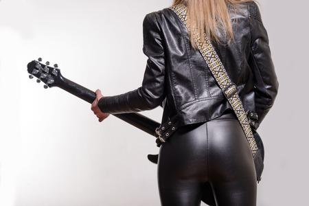 Foto van de achterkant van een vrouwelijke gitarist in lederen jas en broek staan en spelen op een witte achtergrond.