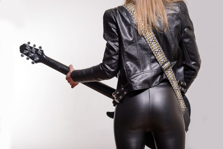 long pants: Photo of the back of a female guitar player in leather jacket and trousers  standing and playing on white background.