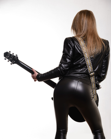 Photo of the back of a female guitar player in leather jacket and trousers  standing and playing on white background.