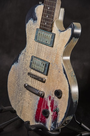 mojo: Aged guitar front on black background