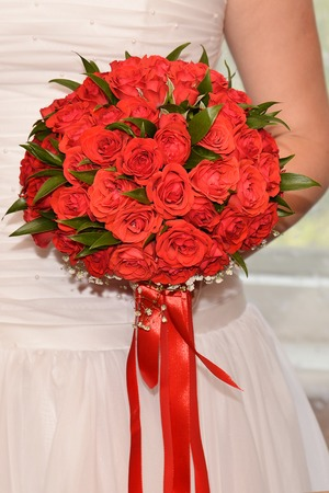 romance rose: wedding bouquet of red roses in the hands of the bride