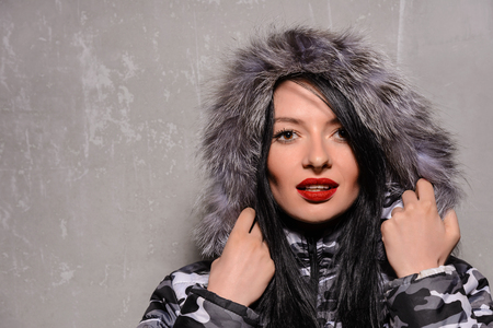 fur hood: Sweet young woman in warm winter jacket with fur hood isolated on grey background.