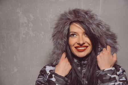 likable: Sweet young woman in warm winter jacket with fur hood isolated on grey background.