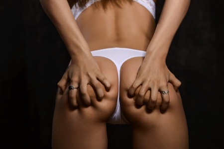 nude butt: Sexy woman buttocks in white panties on black background