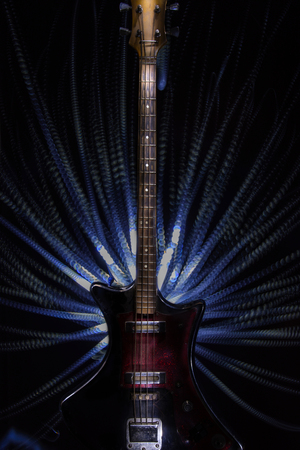 hardrock: old bass guitar on black background. light brush Stock Photo