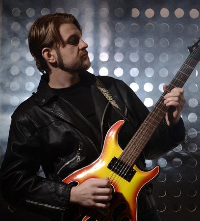 ballad: rock guitarist playing electric guitar in fog