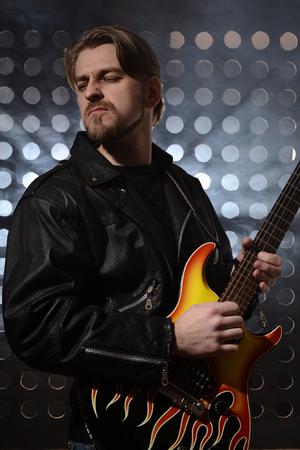 fingering: rock guitarist playing electric guitar in fog