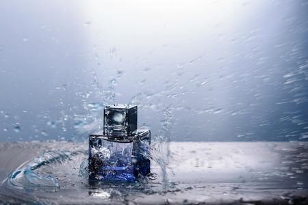 Perfume bottle and water splash around it