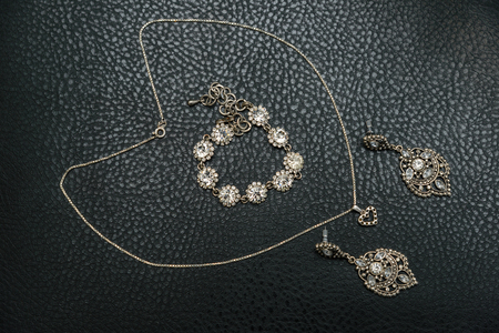 silver jewelry: A set of silver jewelry from chains, rings, signet rings and bracelet on a leather couch