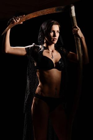 imminence: Chica en una bata de encaje negro con una guadaña de la muerte. concepto