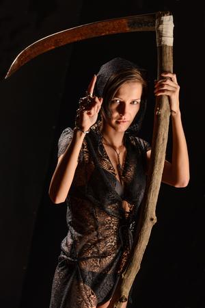 imminence: Chica en una bata de encaje negro con una guada�a de la muerte. concepto