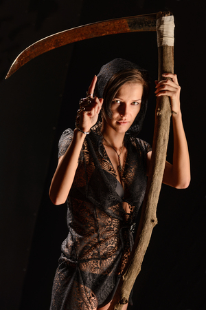 imminence: Girl in a black lace smock with a scythe of death. concept
