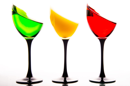 silty: three wine glasses filled with the colors of traffic lights. Stock Photo