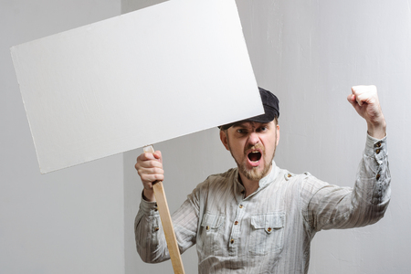 dissatisfaction: Angry protesting worker with blank protest sign. Stock Photo