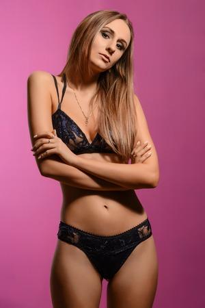 nude blonde girl: Sexy romantic blonde woman posing in delicate lingerie on purple background. Studio shot.