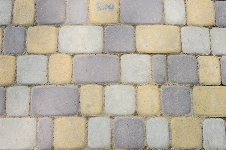road paving: The texture of masonry pedestrian bridge. colored stones. Stock Photo